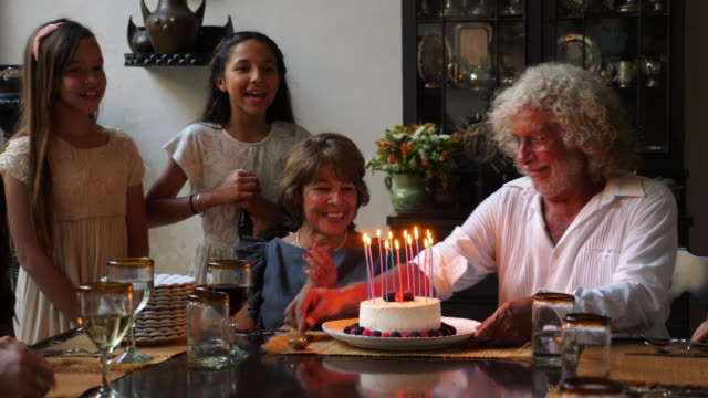 vídeos y material grabado en eventos de stock de ms smiling grandmother admiring birthday cake with candles at dining room table during dinner party with family - cumpleaños