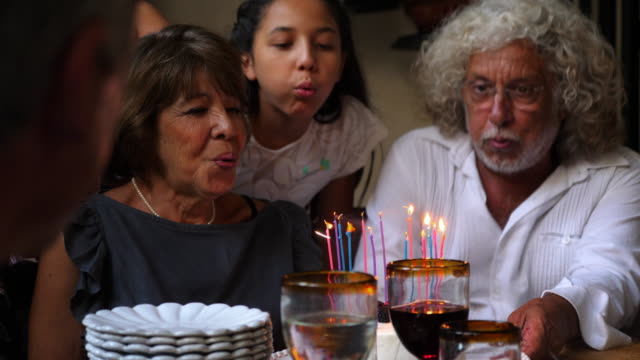 ms smiling grandmother and family blowing out candles on birthday cake during dinner party - compleanno video stock e b–roll
