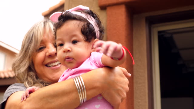 cu smiling grandmother holding baby granddaughter in front of new home on moving day - granddaughter stock videos & royalty-free footage