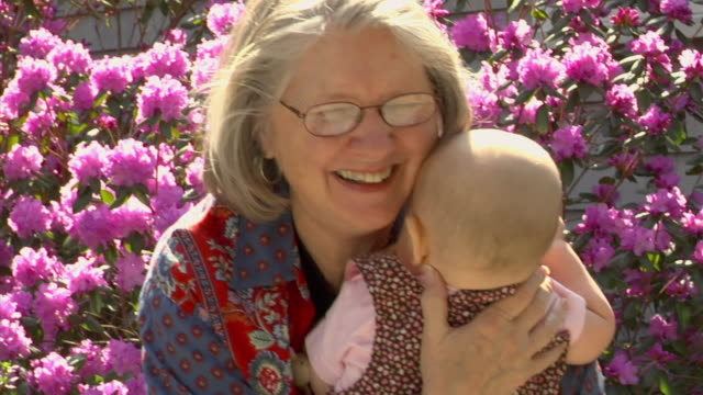 cu, smiling grandmother holding granddaughter (6-11months) outdoors, gloucester, massachusetts, usa - gloucester massachusetts stock videos & royalty-free footage