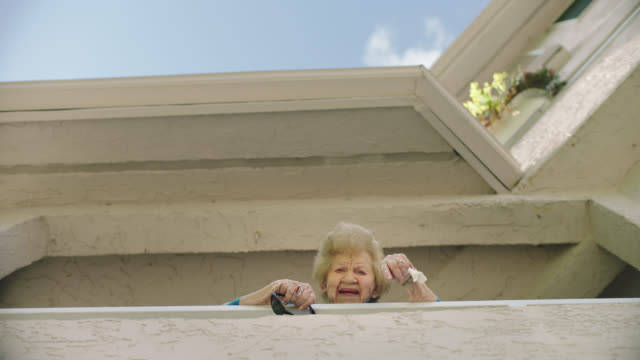 stockvideo's en b-roll-footage met slo mo. smiling grandmother looking down from her balcony. - film moving image