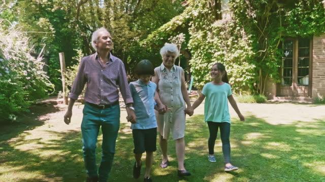 vidéos et rushes de grands-parents souriants retenant la main avec de jeunes petits-enfants - près de