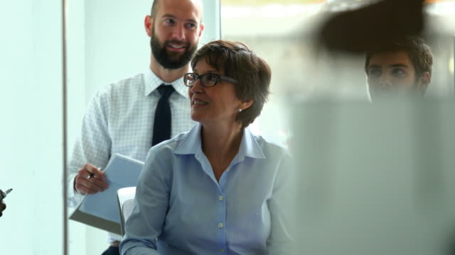 MS Smiling group of businesspeople discussing project details in meeting in conference room