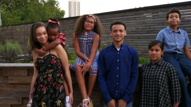 ms smiling group of cousins posing for family portrait after dinner party - america latina stock-videos und b-roll-filmmaterial