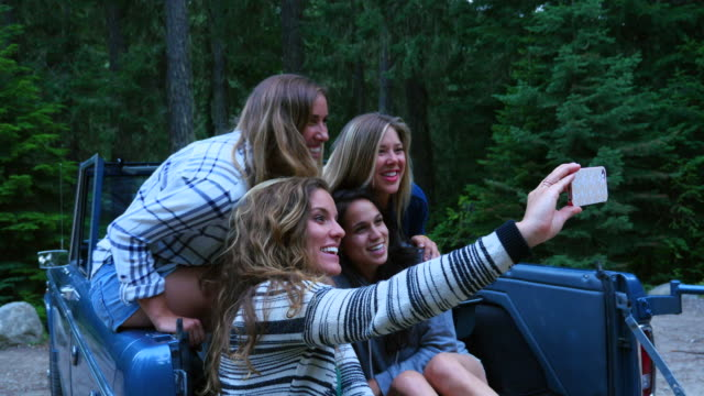 ms pan smiling group of female friends taking self portrait with smartphone in back of convertible off road vehicle in woods - quattro persone video stock e b–roll