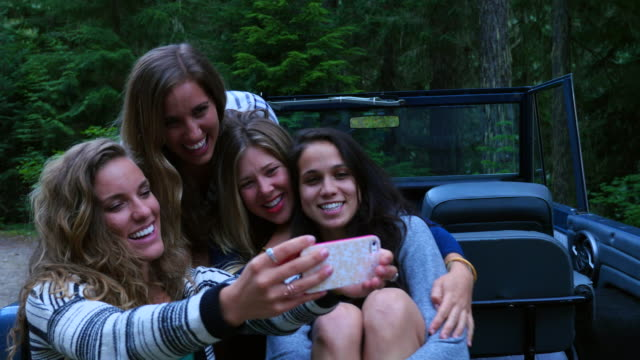 ms smiling group of female friends taking self portrait with smartphone in back of convertible off road vehicle in woods - quattro persone video stock e b–roll