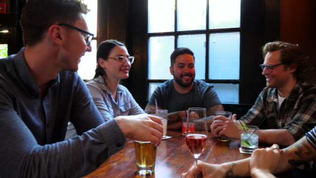 PAN Smiling group of friends in discussion while sharing drinks at table in bar