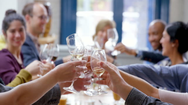ms r/f pan smiling group of friends toasting at dinner party in restaurant - wine glass stock videos and b-roll footage