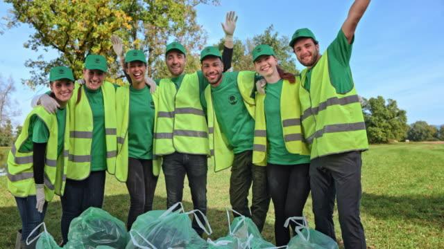 lächelnde gruppe junger freiwilliger posiert auf der wiese, nachdem sie die sanierung abgeschlossen - nachhaltige lebensweise stock-videos und b-roll-filmmaterial