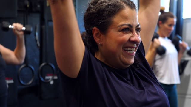 vídeos de stock, filmes e b-roll de ms smiling gym owner encouraging clients during workout in gym - estilo de vida ativo