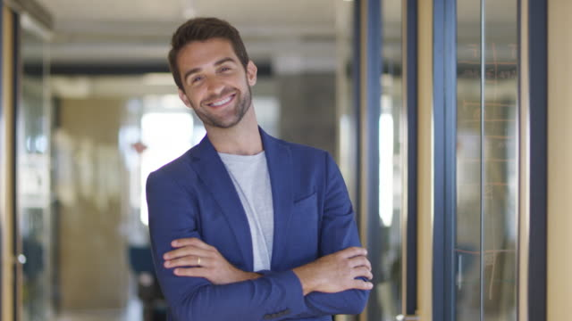 smiling handsome businessman standing in corridor - rivolto verso l'obiettivo video stock e b–roll