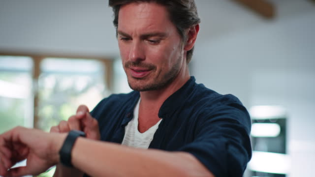 smiling handsome man using smart watch in kitchen - wrist stock videos & royalty-free footage