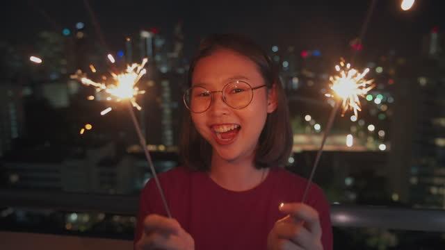 vídeos de stock, filmes e b-roll de sorrindo, momento feliz de jovens mulheres asiáticas segurando com faíscas para uma celebração em uma festa no telhado para relaxar depois de trabalhar duro da geração do milênio. conceito de amizade feminina - 20 29 years