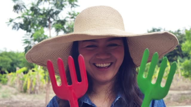 smiling happy woman farmer show her gardening tools equipment - fork hoe leisure activity