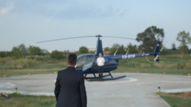 smiling helicopter pilot greeting passenger with luggage - helipad stock videos & royalty-free footage