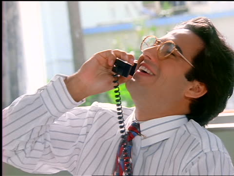 vidéos et rushes de smiling hispanic businessman with eyeglasses talking on telephone in office - 1990 1999