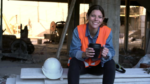 smiling hispanic female engineer holding coffee mug at site - construction worker stock videos & royalty-free footage