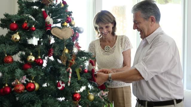 vidéos et rushes de aînés hispaniques de sourire décorant l'arbre de noel - décoration de noël