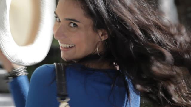 Smiling Hispanic woman holding hat