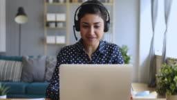 Smiling indian woman wear wireless headset video calling on laptop