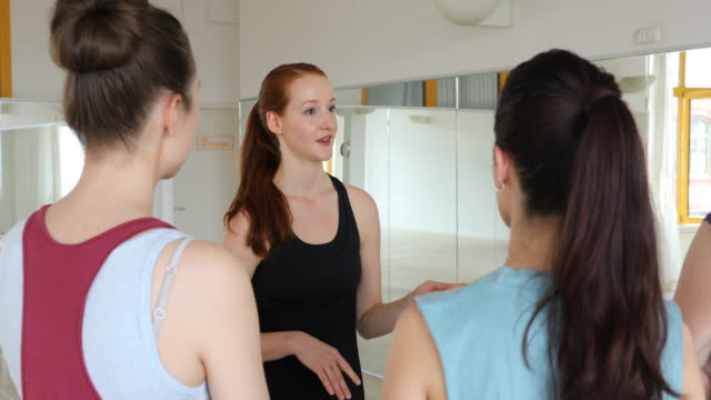 Smiling instructor talking to women at yoga class