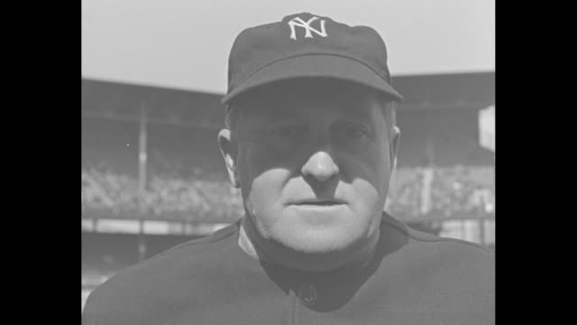 Smiling Joe McCarthy manager of the New York Yankees stands in sunlight removes hat during game at Yankee Stadium