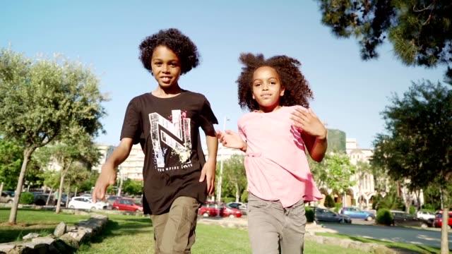 vídeos de stock, filmes e b-roll de miúdos de sorriso que funcionam no parque - vista de ângulo baixo