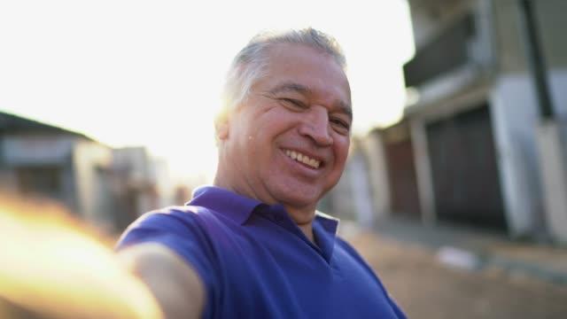 smiling latin senior man taking a selfie on the street - photo messaging stock videos & royalty-free footage