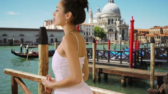 smiling latina tourist in white sundress watches gondolas on grand canal - sundress stock videos & royalty-free footage