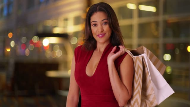 smiling latina woman holding shopping bags over shoulder outdoors in evening - red dress stock videos & royalty-free footage