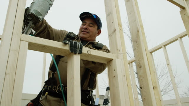 a smiling latino man in his forties uses a pneumatic nail gun to secure a wooden two-by-four in a house frame outside on a cold winter day - work tool stock videos & royalty-free footage