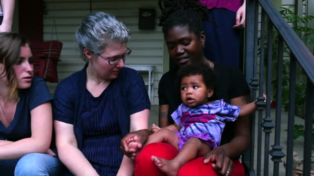 ms zo smiling lesbian couple sitting on front porch with family on summer evening - adoption stock videos & royalty-free footage
