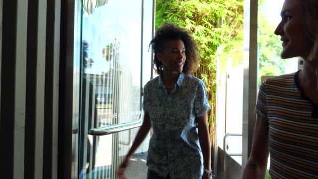 vidéos et rushes de ts smiling lesbian couple walking into hotel lobby carrying luggage - porte structure créée par l'homme