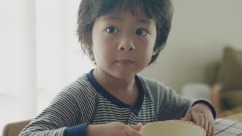 vídeos y material grabado en eventos de stock de niño sonriente comer cerca - vida sencilla
