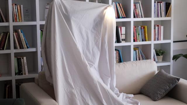 vidéos et rushes de petit garçon de sourire se cachant sous la couverture - linge de lit