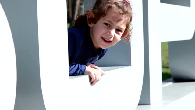 smiling little girl girl looks out of the big plastic letter o - hide and seek stock videos & royalty-free footage