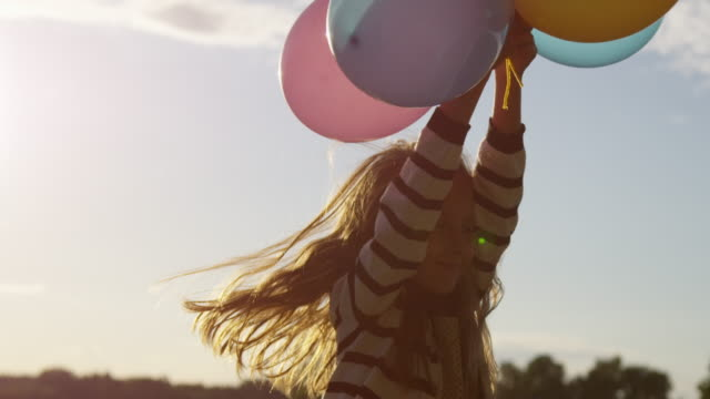 Smiling Little Girl Holding Air Balloons in Hands Outdoors