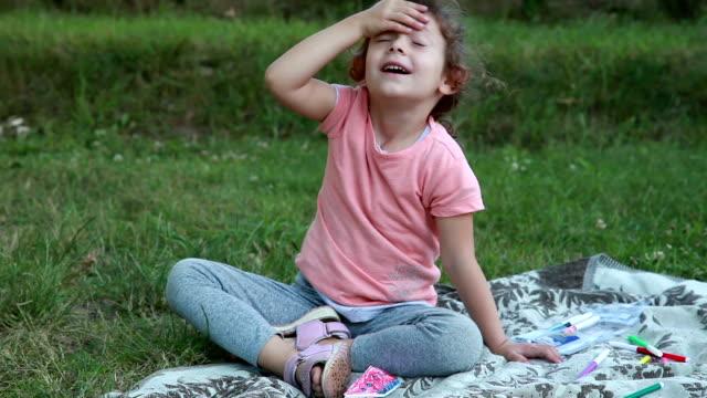 vidéos et rushes de sourire de petite fille caressant son visage - se mordre les lèvres