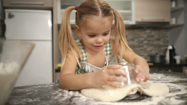Smiling little girl using drinking glass on raw dough and making round shapes.