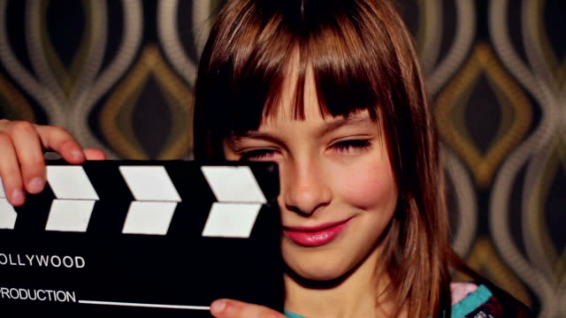 smiling little girl with a film slate - film slate stock videos & royalty-free footage