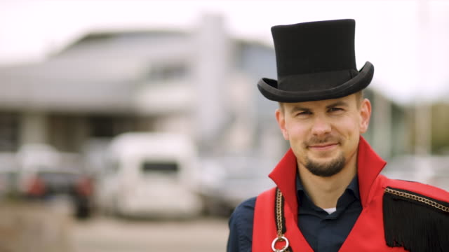 smiling magician in black top hat and red stage costume looks at camera - top hat stock videos & royalty-free footage