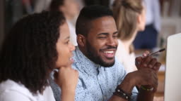 Smiling male african employee listening female colleague sitting in office