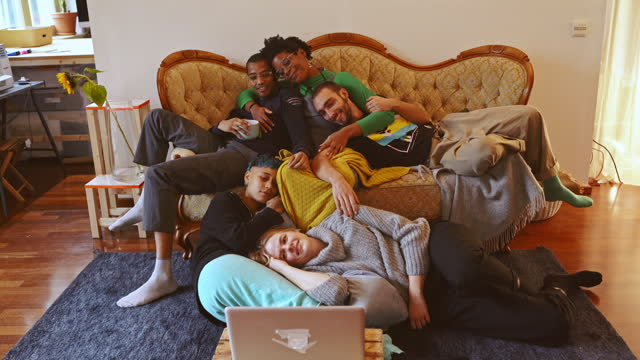 smiling male and female friends watching movie in living room - five people stock videos & royalty-free footage