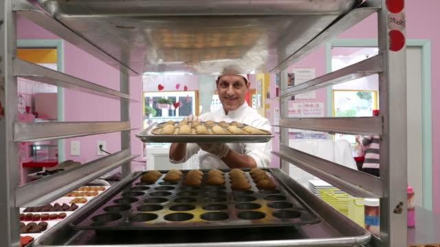 smiling male baker bringing baking tin to cooling rack - baking stock videos & royalty-free footage