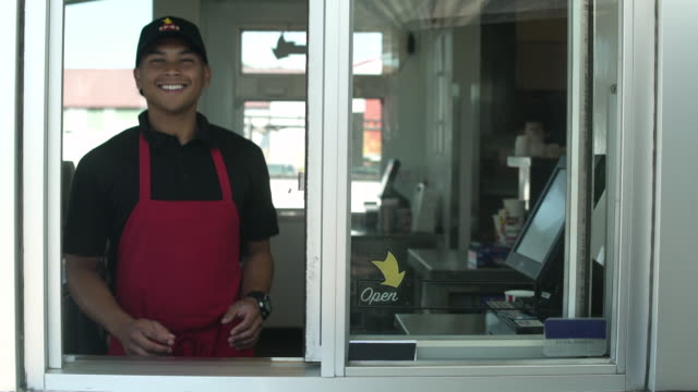 smiling male cashier of a fast food restaurant looking at camera - fast food restaurant stock videos & royalty-free footage