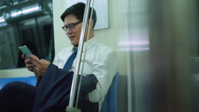 smiling male commuter texting messages on mobile phone in subway train - good news stock videos & royalty-free footage