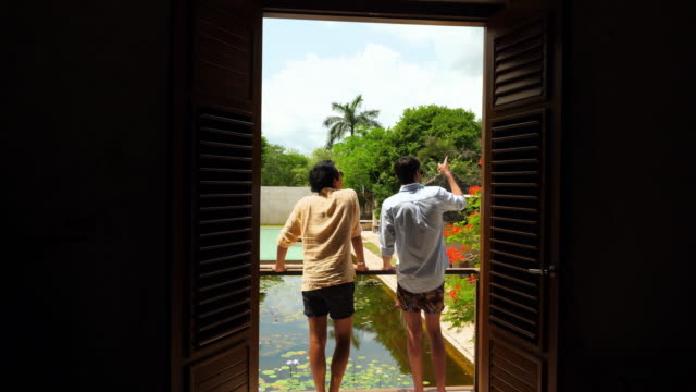 vídeos y material grabado en eventos de stock de ms smiling male couple in discussion while standing on balcony of room overlooking courtyard of luxury tropical resort - prosperidad
