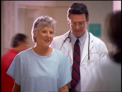 Smiling male doctor + senior woman in hospital gown talking + walking down hallway in hospital