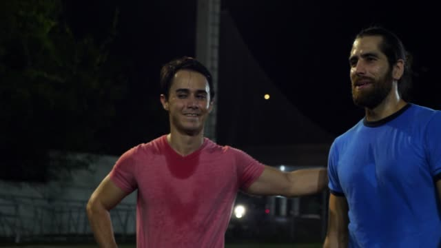 vídeos de stock e filmes b-roll de ms smiling male friends in discussion during evening soccer game - amizade masculina
