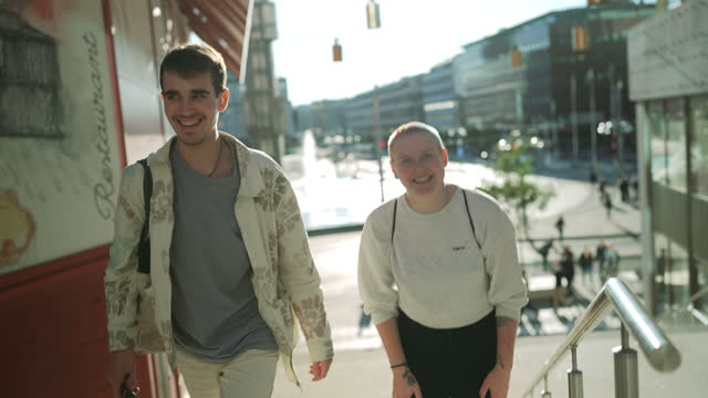 stockvideo's en b-roll-footage met smiling male friends talking while climbing steps on sunny day - sunny